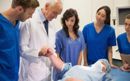 Medical students and professor checking pulse of student at the university